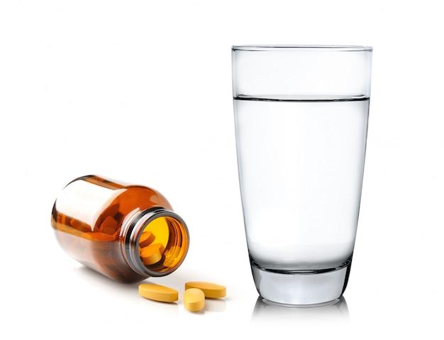 Pillole dalla bottiglia e dal bicchiere d'acqua isolati su bianco