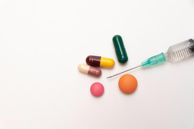 Pillole degli antibiotici dei prodotti farmaceutici, pillole della medicina e capsule e siringa su bianco.