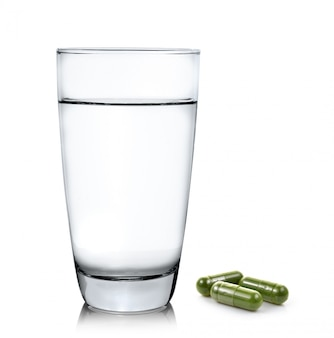 Pillole della capsula del moringa e del bicchiere d'acqua