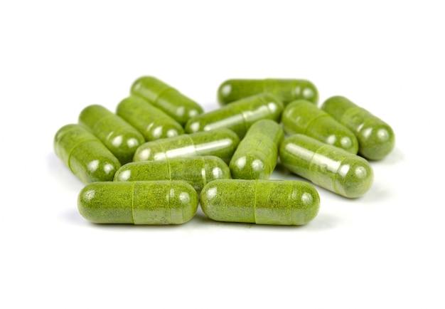 Pillole della capsula di moringa su fondo bianco