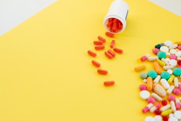 Pillole della medicina farmaceutica pillole in bottiglia della medicina sulla parete gialla supplementi delle vitamine. concetto sano supplemento nutrizionale droghe mediche assortite spazio della copia