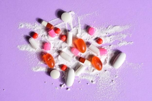 Pillole delle capsule rotte con il vostro farmaco della polvere su fondo viola