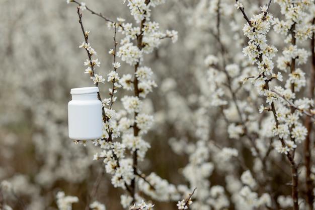 Pillole di allergia contro lo sfondo di piante fiorite