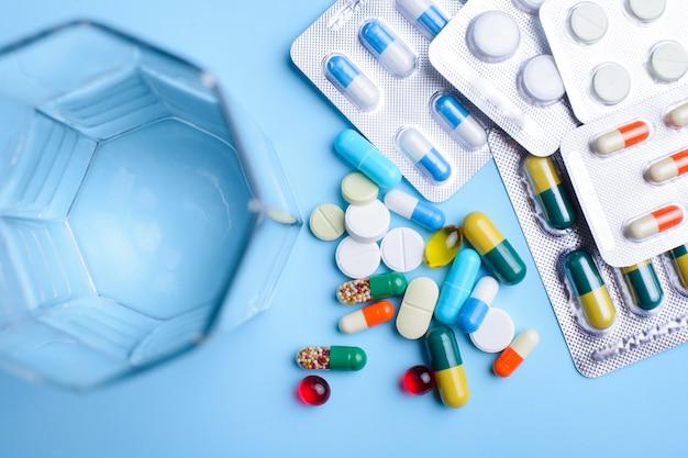 Pillole di diverse dimensioni e colori confezionate in una confezione di alluminio e non imballate vicino a un bicchiere d'acqua