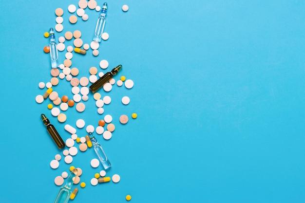 Pillole di diversi colori e fiale con medicina su sfondo blu. concetto di industria farmaceutica, medicina, trattamento e recupero dopo la malattia. vista piana, vista dall'alto