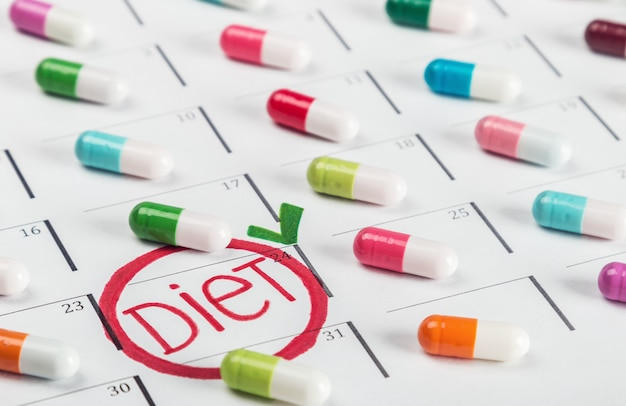 Pillole di diversi colori si trovano sul piano di dieta