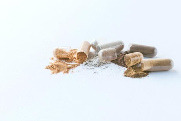 Pillole di erbe apra le capsule e la polvere di erbe su priorità bassa bianca.