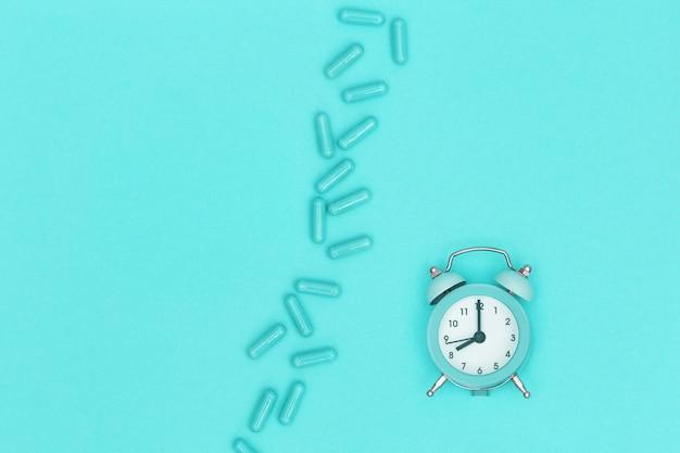 Pillole di medicina farmaceutica, capsula e orologio per controllo del tempo si trovano su carta color menta. assistenza sanitaria. sfondo medico. vista dall'alto. copia spazio