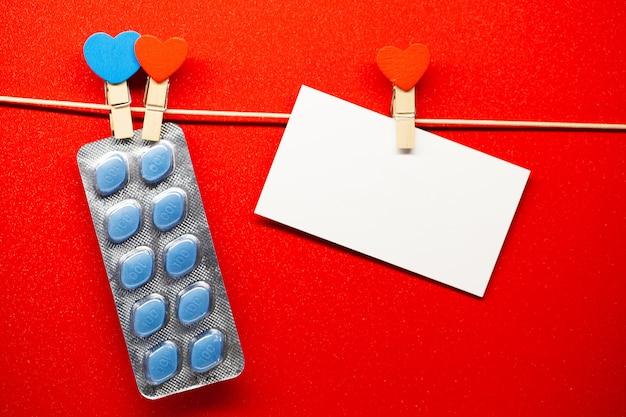 Pillole di salute sessuale per uomini appesi su una corda e una carta bianca vuota