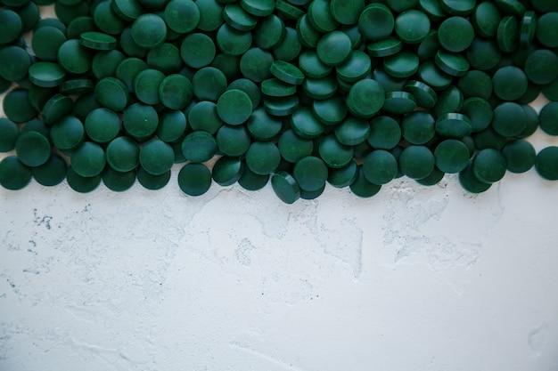 Pillole di spirulina verde su un bianco.