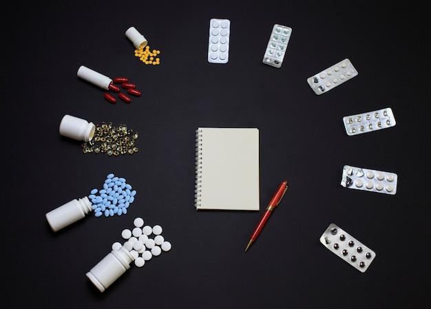 Pillole differenti con il taccuino e matita sul nero