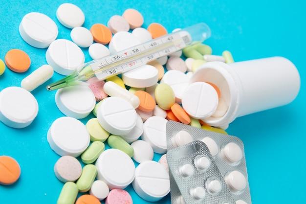 Pillole, droghe e antibiotici delle medicine su un fondo blu. medicina e assistenza sanitaria.