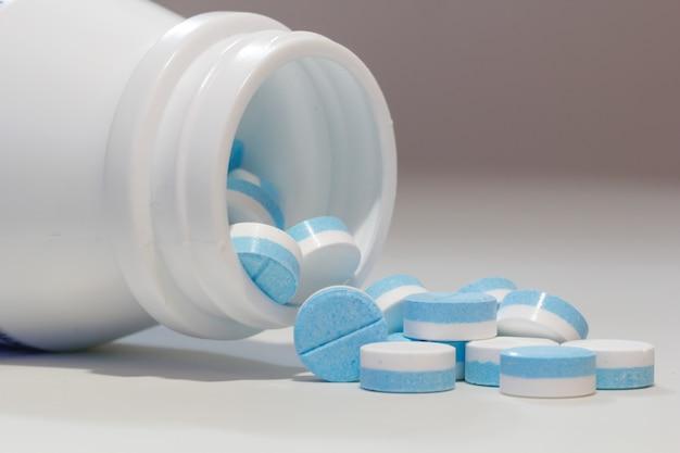 Pillole e bottiglia di pillola blu e bianche sulla tavola bianca.