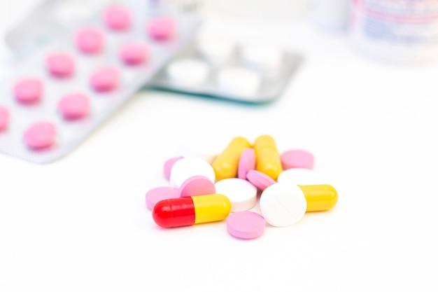 Pillole e capsule di diversi colori il concetto di assistenza sanitaria, trattamento, malattia.