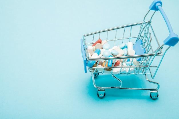 Pillole e carrello della spesa su sfondo blu. idea creativa per il costo dell'assistenza sanitaria, farmacia, assicurazione sanitaria e concetto di business dell'azienda farmaceutica. copia spazio.