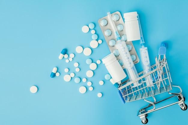 Pillole e iniezione medica nel carrello della spesa su sfondo blu. idea creativa per il costo dell'assistenza sanitaria, farmacia, assicurazione sanitaria e concetto di azienda farmaceutica. copia spazio.