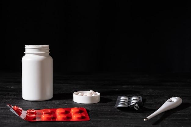 Pillole e termometro medici sulla superficie di legno nera. concetto di auto trattamento: immagine scura minimalista di farmaci da prescrizione.