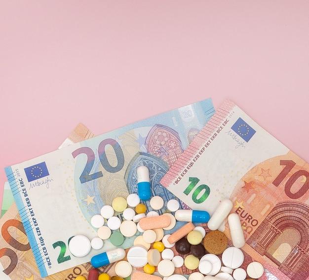 Pillole ed euro su uno sfondo rosa con copia spazio. focalizzazione morbida. concetto di medicina, denaro e salute.