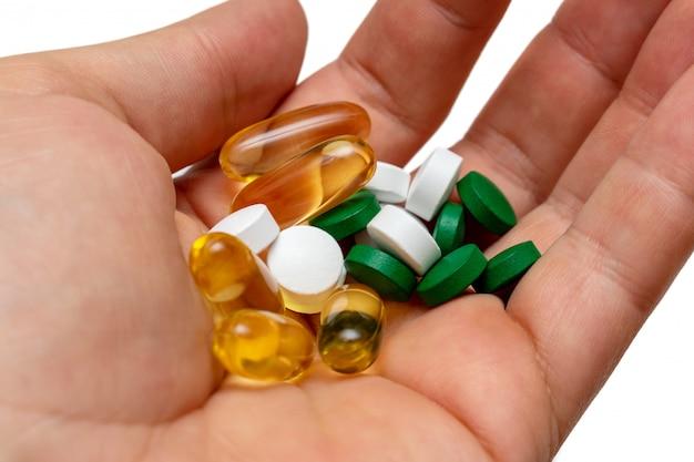 Pillole gialle dell'olio di pesce di omega 3 della vitamina e in una mano sulla fine isolata bianca su