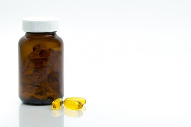 Pillole gialle della capsula dell'olio di pesce con la bottiglia di vetro ambrata con l'etichetta in bianco sulla tavola con lo spazio della copia per testo