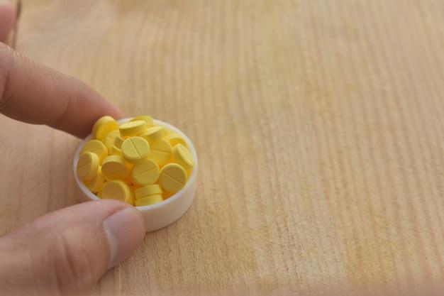 Pillole gialle sulla tavola di legno