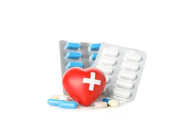 Pillole in blister e cuore isolati su fondo bianco