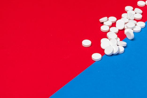 Pillole mediche bianche su una priorità bassa rossa e blu di due colori