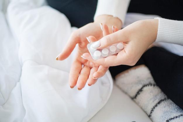 Pillole mediche. donna che estrae una pillola dal blister
