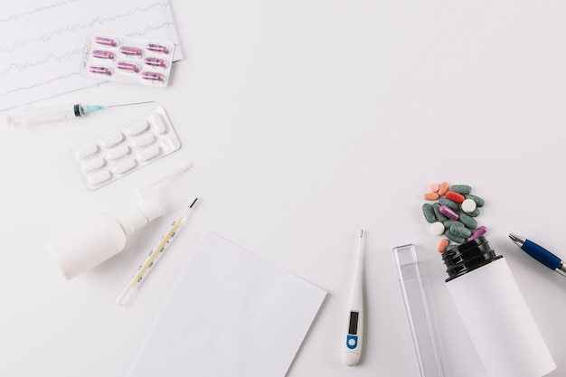 Pillole mediche; siringa e termometro isolato su sfondo bianco