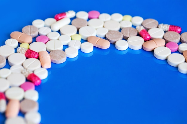 Pillole multicolori su sfondo blu, medicina e salute