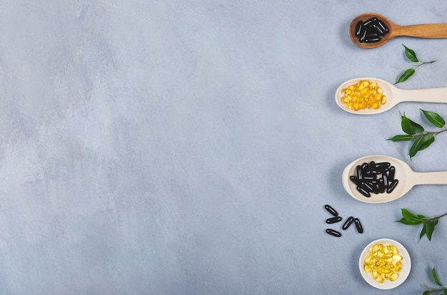 Pillole nere e gialle sul cucchiaio di legno su fondo grigio