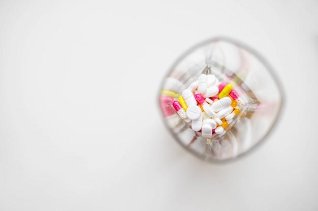 Pillole o capsule della medicina in vetro su fondo bianco. prescrizione di droga per i farmaci di trattamento. farmaco farmaceutico.
