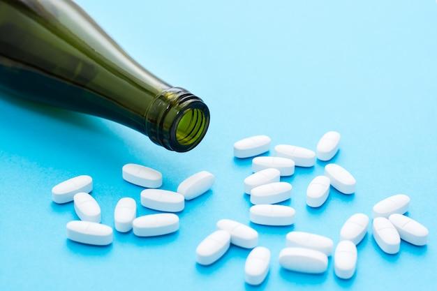 Pillole ovali bianche una bottiglia di vino vuota sul blu. concetto di trattamento farmacologico per l'alcolismo.