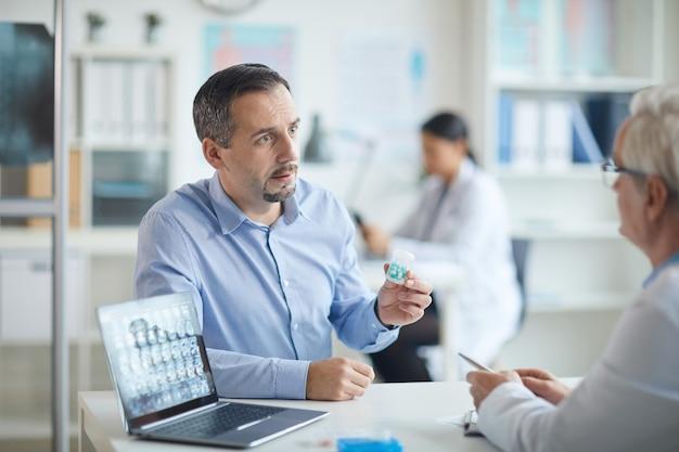 Pillole pazienti della tenuta e parlare con medico