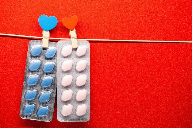 Pillole per la salute sessuale per uomini e donne appesi a una corda