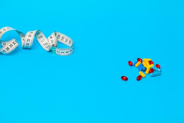 Pillole per perdita di peso e misura di nastro sul blu.