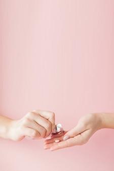 Pillole rosa compresse nella mano della donna su sfondo rosa. concetto di medicina.
