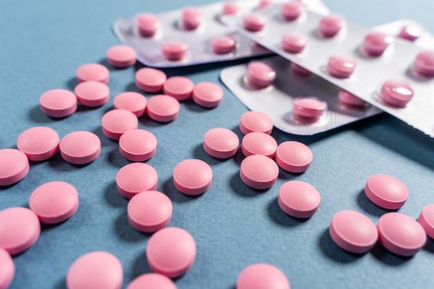 Pillole rosa luminose su fondo colorato blu scuro