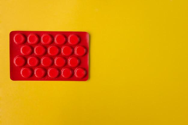 Pillole rosse del medicamento su giallo