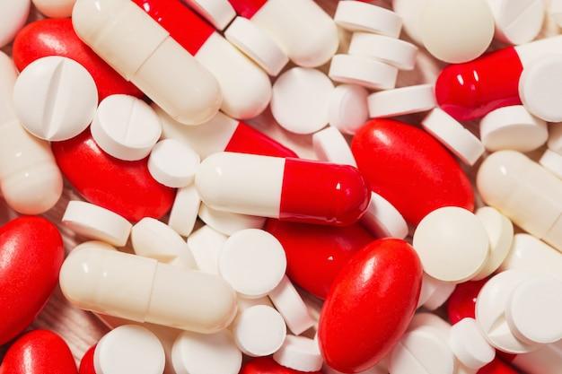 Pillole rosse e bianche sulla tavola di legno