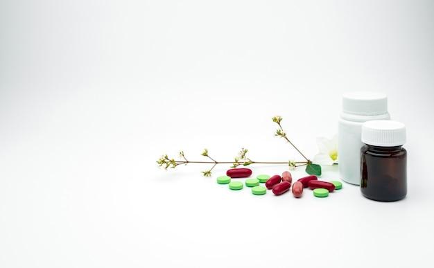 Pillole rosse e verdi di compresse e capsule di integratori con fiori e ramo con etichetta in plastica vuota, bottiglia di vetro ambrata su sfondo bianco con spazio di copia, basta aggiungere il tuo testo