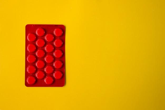 Pillole rotonde bianche nell'imballaggio rosso sul giallo