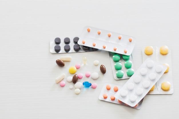 Pillole sul tavolo di legno bianco