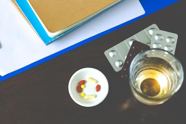 Pillole variopinte e medicine sulla tavola con la lista di controllo di salute