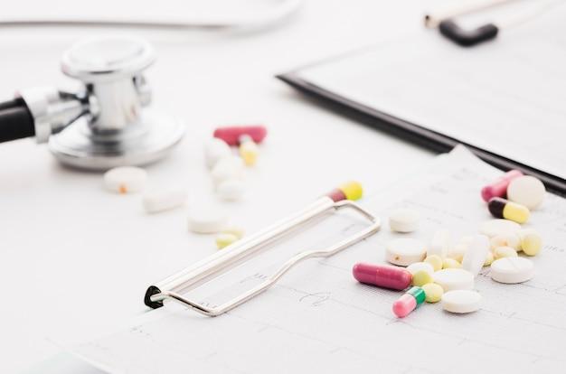 Pillole variopinte sopra il grafico e lo stetoscopio del ecg su priorità bassa bianca
