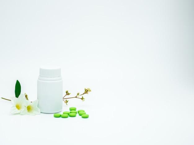 Pillole verdi della compressa di supplemento e della vitamina con il fiore e ramo e bottiglia di plastica dell'etichetta in bianco su fondo bianco con lo spazio della copia, appena aggiunga il vostro testo