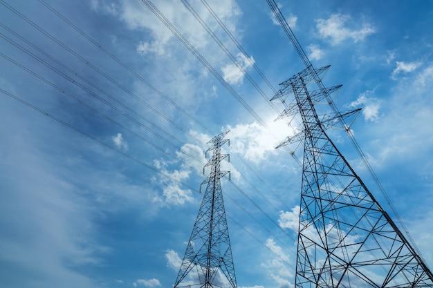 Pilone elettrico ad alta tensione e cavo elettrico contro cielo blu e le nuvole bianche.