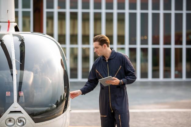 Pilota commerciale dell'uomo in vestito del tecnico che sta davanti all'elicottero dopo il motore di controllo e manutenzione