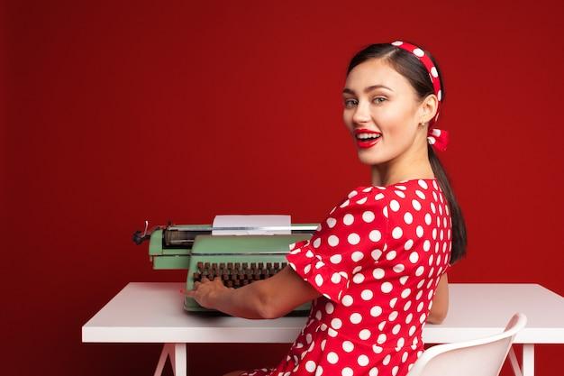 Pin up girl digitando su una macchina da scrivere