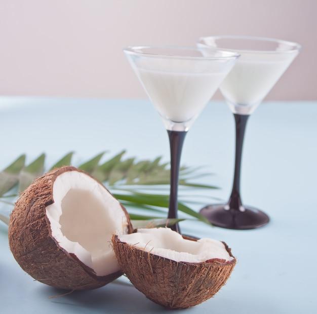 Pina colada cocktail sul tavolo blu con foglia di palma e cocco sullo sfondo